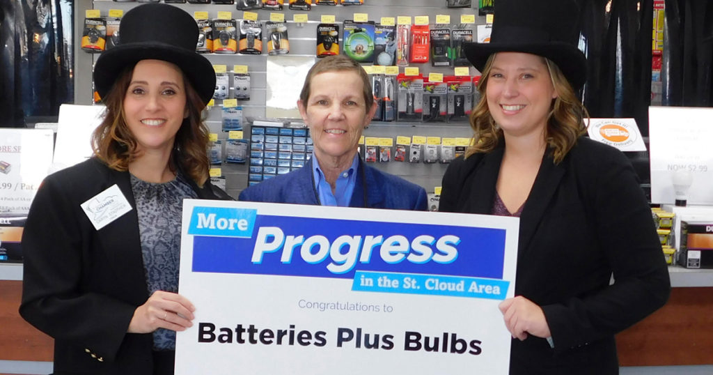"Two women wearing black top hats and coats flank a franchisee Bernie Perryman, the woman in a blue shirt and blazer. All three are smiling and holding up a sign that reads, ""More Progress in the St. Cloud area. Congratulations to Batteries Plus Bulbs."