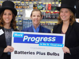 Two women wearing black top hats and coats flank a woman in a blue shirt and blazer. All three are smiling and holding up a sign that reads,