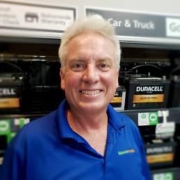 Ralph Badtram standing infront of car and truck batteries