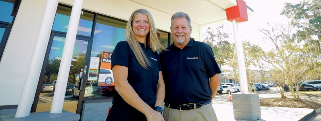 Husband and wife franchisees Brenda and Rick Phipps, standing in front of a Batteries Plus store.