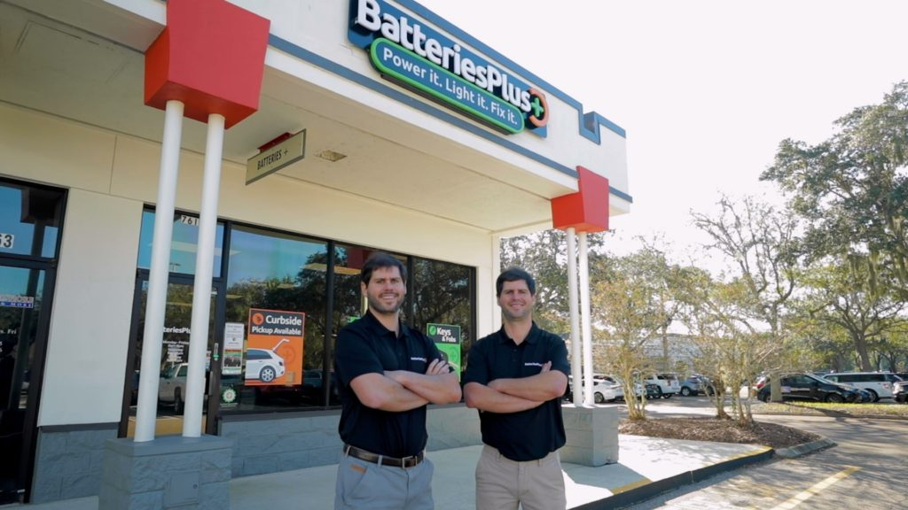 Two franchisees, Javier and Alejandro, are standing in front of a Batteries Plus store.