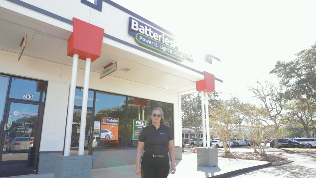 A Batteries Plus franchisee, Ingrid Brummett, standing in front of a storefront.