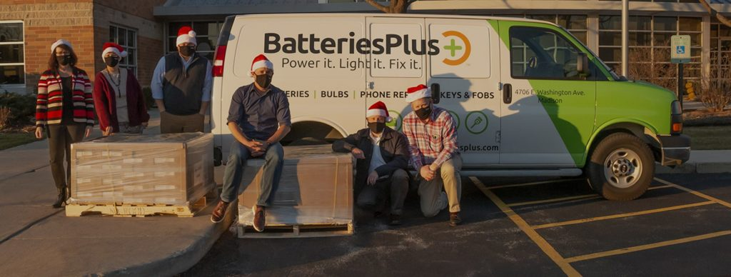 Batteries Plus employees in Christmas hats sitting on pallets of toys in front of a Batteries Plus van