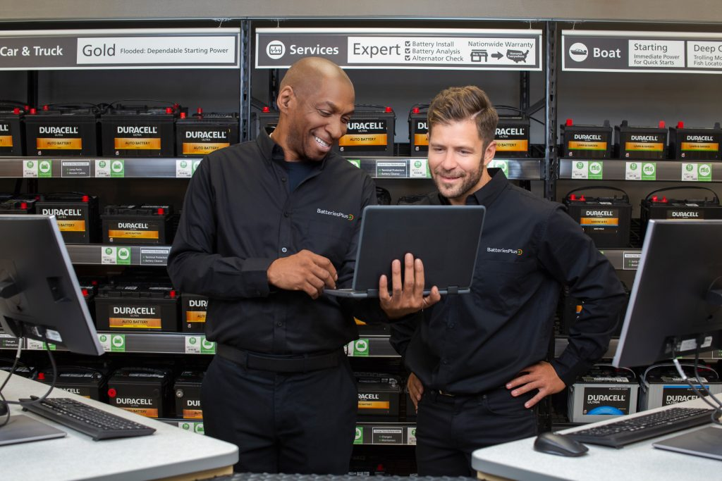 Batteries Plus employee holding a laptop with a colleague