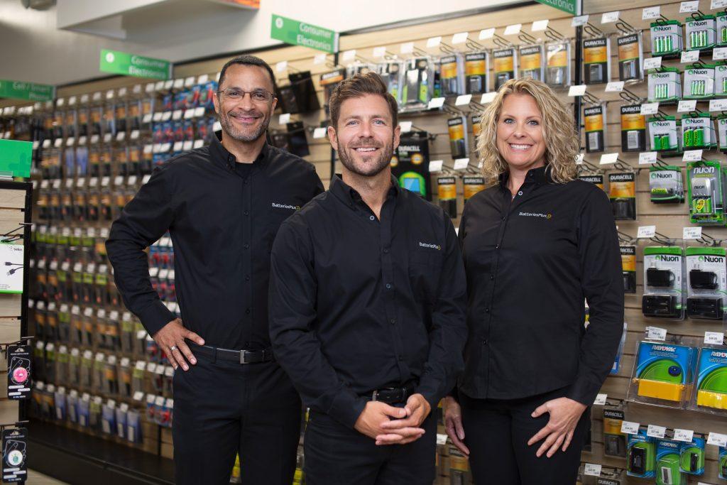 Batteries Plus team standing along the store aisle